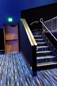 An aisle runs across the width of the auditorium, ending in an exit door. At both ends of the aisle are stairs to the upper seating section. - , Utah