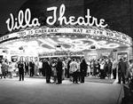 Moviegoers stand beneath the circular marquee at night.