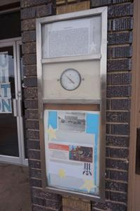 A tall poster case on the right side of the entrance includes a history of the theater, a thermometer, a historical photo, and information on the current attraction. - , Utah