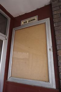 An empty 'Now Showing' poster case on the right side of the entrance doors. - , Utah