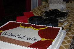 On a table is a cake decorated as stage with the curtains parted to reveal the words, 'The Show Must Go On!'