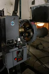 35mm film enters the projector at the top, passes in front of the lens, and exits through an optical sound reader at the bottom.