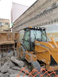 An excavator on the east side of the Utah Theatre, with new framing towards the rear of the building.