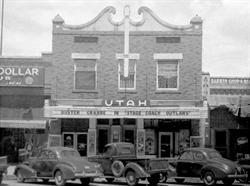The two-story front facade of the Utah Theatre, with a flat attraction board over the entrance and vintage cars parked in front.