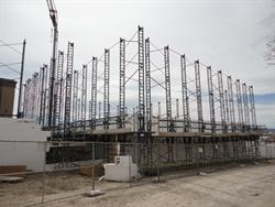 Scaffolding surrounds a new auditorium as its walls begin to rise.