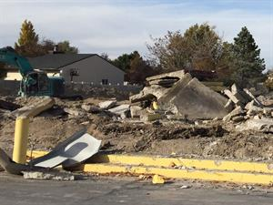 Piles of concrete slabs sit on the ground as excavators continue to dig through the rubble. - , Utah
