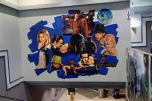 A mural above the main staircase includes <em>Gone With the Wind</em>, <em>The Ten Commandments</em>, <em>E. T.: The Extra-Terrrestrial</em>,<em> Star Wars</em>, and <em>Indiana Jones</em>.