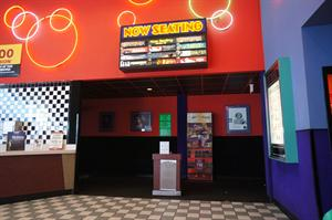 A ticket-taker's stand in the middle of the entrance to the theater hallway. Above is a 'Now Seating' sign. The light behind each title turns on when the movie is ready for seating. - , Utah