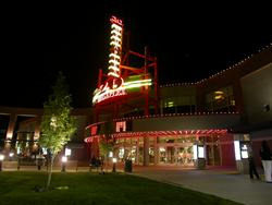 Theater entrace at night.  Above the wide, circular entrance is are two electronic attraction boards