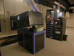 A digital project appears on the left, with a rack of equipment in the background.