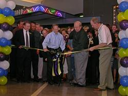 Larry H. Miller tries to cut the ribbon with a large pair of scissors.