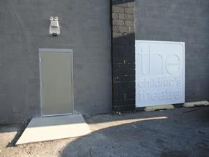 The old Childrens Theatre sign from downtown Salt Lake stands next to a new auditorium exit door on the north side of the building. - , Utah