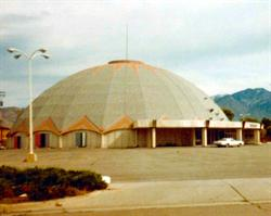 The domed building of Century 22, with a car parked in front and the exterior doors of one auditorium open.