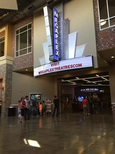 A Megaplex marquee hangs over the entrance to the main theater hallway.  A two-line attraction board directs moviegoers to the Megaplex web site. - , Utah