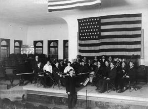 Mose Gudmansen leads an orchestra in a little theater on the east end of the top floor of the College Building.  This photo shows the stage before a permanent proscenium arch was installed in 1930. - , Utah