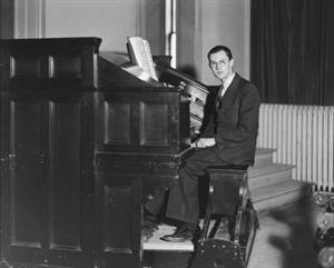 J. J. Keeler practices the organ in the College Hall Recital Hall in 1936.  The proscenium arch on the left side of the stage is visible in the top left of the photo.  Heavy velour drapes cover a windw in the top right. - , Utah