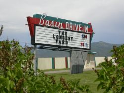 The sign of the Basin Drive-In has a large red arrow pointing towards the theater's entrance.