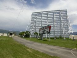 The entrance of the Basin Drive-In, with the screen tower, sign, and ticket booth. - , Utah