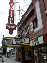 Front of the Capitol Theatre, showing the vertical blade sign and marquee  The Capitol Theatre has a tall, vertical sign attached to the front of the building, with a triangular marquee that extends over the sidewalk. - , Utah