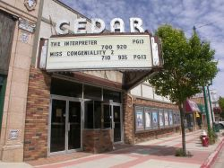 The Cedar Twin theater has a triangular marquee with a five-line attraction board and the name of the theater, 'Cedar'. - , Utah