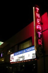 The Country Club Theatre has a vertical sign with the word 'Theatre' on it and, above the entrance, an attraction board with the name 'Country Club Theatre'. - , Utah