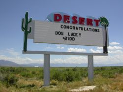 The sign of the Desert Drive-In has five-line attraction board with the word 'Desert' above and a cactus and a palm tree on either side. - , Utah