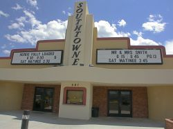 The entrance of the Southtowne Cinema has two sets of doors with an attraction board above each.  Above the ticket booth, in vertical letters, is the name of the theater. - , Utah