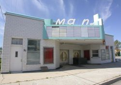 The Main Theatre in Garland, Utah.  The double-sided marquee extends partially over the sidewalk and features the name of the theater, 'Main', above an attraction board. - , Utah