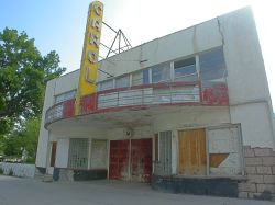 The front of the Carol Theater features a circular marquee with a vertical sign with the name 'Carol'.  Above the marquee is a row of second-floor windows. - , Utah