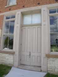 The original entrance of the opera house has two tall wooden doors flanked by windows. - , Utah