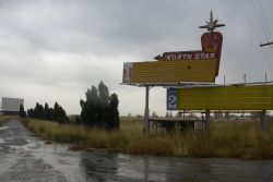 The entrance of the North Star Drive-In, with the theater's sign on the right and the remaining screen in the distance on the left. - , Utah