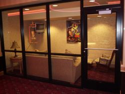 In the main hall of the Redstone Cinemas is a small waiting room with glass walls, a wall-mounted television, a couch and chair, and a poster of 'Toy Story'. - , Utah