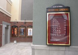 A 'Now Showing' poster case for the Redstone Cinemas lists all the movies an their showtimes. - , Utah