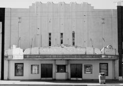 'Front facade is the best example of Art Deco style in Brigham City. . .   Strong vertical features in upper front facade include lighting fixtures and three vertical rows of small windows.  Lower facade is ceramic tile (yellow with green and blue trim); upper facade is painted light green.  Most remarkable feature is 'Roxy' marquee.'