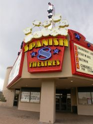 The sign of the theater is a popcorn bucket with the name 'Spanish 8 Theatres' written on it in neon letters. - , Utah