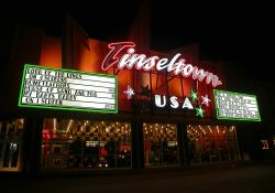 The marquee and attraction boards of the Tinseltown, USA at night.