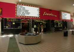 The entrance of the Cinemark Tinseltown theater is inside the Newgate Mall in Ogden, Utah.  The theater has three ticket booths with two ticket windows each.  Above them is the name of the theater, 'Tinseltown', with attraction boards on either side. - , Utah