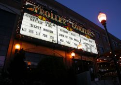 The sign of the Trolley Corners Theatres at night.  The words 'Trolley Corners' appear at the top of the sign and 'Theatres' is written on either end.  Below the name of the theater were sections for each theater with seven lines of copy.