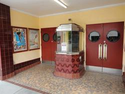 The entrance of the theater has a box office in the center with double doors on either side. - , Utah
