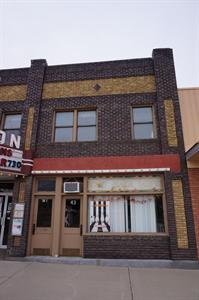 The storefront on the right side has a sign for 'The Hair Loft' in the window.  Behind the left door is a stairway leading to the second floor. - , Utah