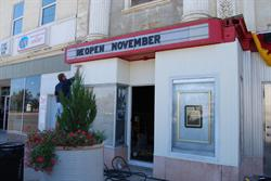 A man paints the front of the shop space on the left of the entrance of the Casino Star Theatre.  Above him, the attraction board reads,