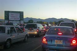 Cars wait in line at the Redwood Drive-in.  On the left is a banner on the back side of a screen tower. - , Utah