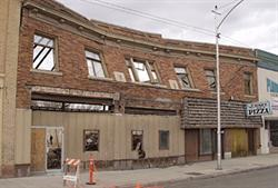 The two-story, brick facade of the Venice Theater, just before demolition on 5 March 2001.  Three poster cases in the middle lead to the theater entrance on the left.  A pizza shop was on the right end of the building. - , Utah