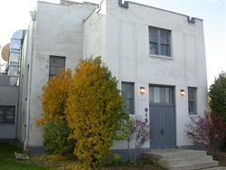 Tall bushes grow on either side of the entrance of the former Shire West Theatre. - , Utah