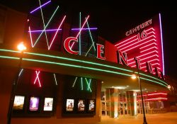 Neon on the front of the theater at night.  On the left side of the entrance are six poster cases, with flashing multi-colored lights above them.  On the right side is an outside ticket window and a tall tower bearing the name 'Century 16'. - , Utah
