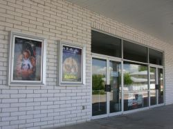 Two poster cases on the left side of the Plaza Twin entrance.  The entrance has one set of entrance doors and another set for exit.  The theater is closed on Sundays. - , Utah