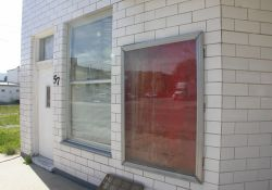 On the left of the Main Theatre's entrance is an empty poster case and the window and door of a small shop. - , Utah