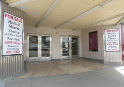 The entrance of the Murray Theatre has two sets of doors with movie poster cases on either side. - , Utah