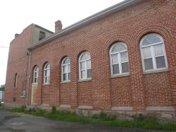 A row of windows along the west side of the building.  Below the last window is a newer exit door. - , Utah