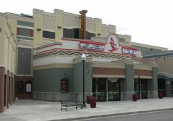 The front of the Redstone 8 Cinemas features a vertical sign with the name of the theater.  The small plaza in front of the entrance lamp posts and park benches. - , Utah